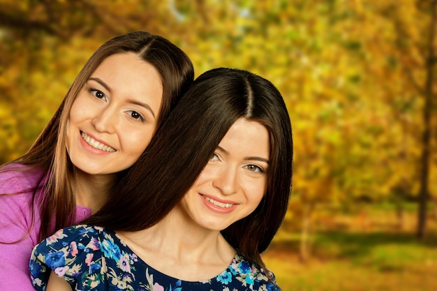 Deux jumelles gaies de filles, dans le parc d'automne de rue
