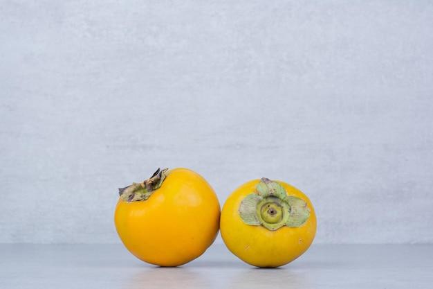 Deux kakis doux frais sur fond blanc. photo de haute qualité