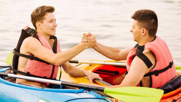 Deux kayakistes assis face à face, tenant la main de l'autre