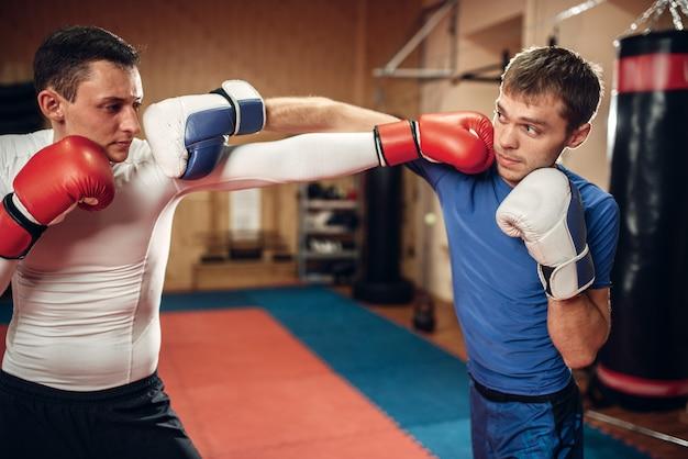 Deux kickboxers mâles pratiquant sur l'entraînement en salle de sport