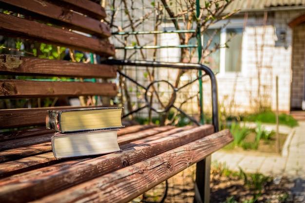 Deux livres épais allongés sur un banc de bois dans la cour