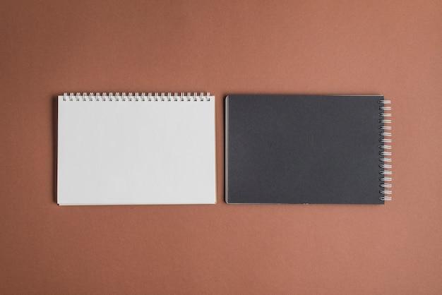 Deux livres en spirale sur toile de fond marron