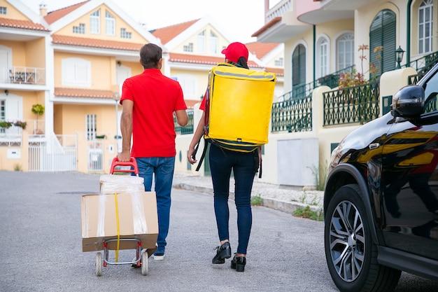 Deux livreurs marchent et cherchent une adresse. vue arrière des courriers adultes livrant la commande dans un sac isotherme et des boîtes en carton sur chariot. service de livraison, concept de poste et d'expédition