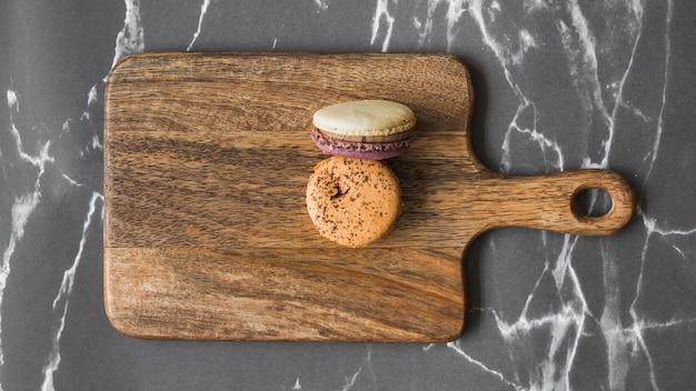 Deux macarons sur une planche à découper en bois sur le fond de marbre