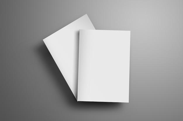 Deux magazines a4, (a5) fermés vierges avec des ombres douces et réalistes isolées sur une surface grise. l'une des brochures se trouve à un angle de la deuxième brochure.