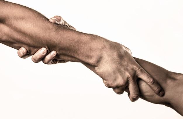 Deux mains, bras aidant d'un ami, travail d'équipe. concept de coup de main et journée internationale de la paix, soutien. main tendue, bras isolé, salut. gros plan sur la main d'aide.