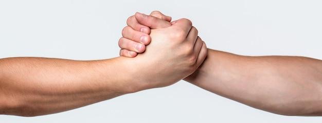 Deux mains, bras aidant d'un ami, travail d'équipe. main tendue, bras isolé, salut. poignée de main amicale, salutation d'amis, travail d'équipe, amitié. sauvetage, geste d'aide ou mains