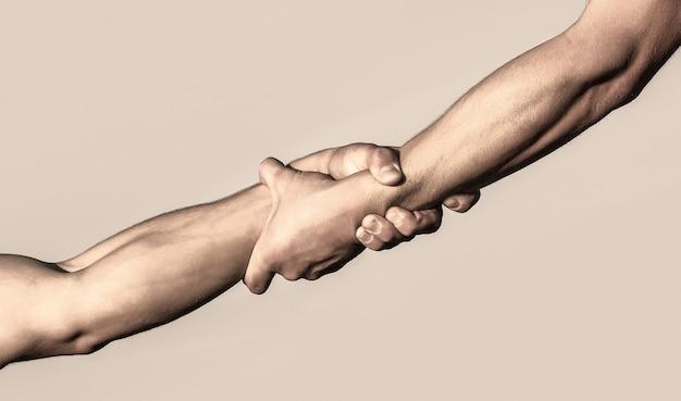 Deux mains, bras aidant d'un ami, travail d'équipe. sauvetage, geste d'aide ou mains. gros plan sur la main d'aide. concept de coup de main, soutien.