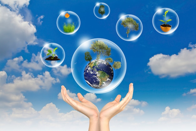 Deux mains avec des bulles contenant des mondes au sein