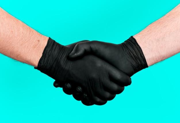 Deux mains dans un gant noir en latex faisant une poignée de main entre deux personnes