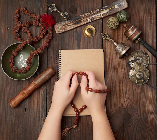 Deux mains dans une prière posent sur une table en bois marron au milieu des outils de méditation tibétains vintage
