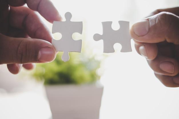Deux mains essayant de connecter une pièce de puzzle couple
