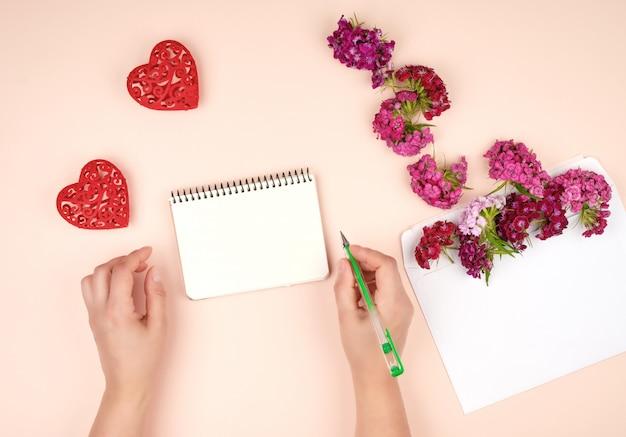 Deux mains féminines et un cahier à spirale ouvert avec des feuilles blanches vierges