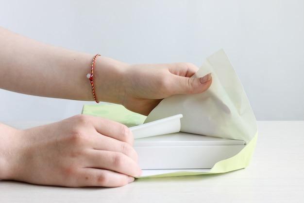 Deux mains féminines décollent les emballages des boîtes sur un fond clair