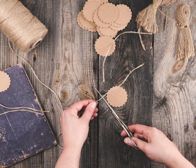 Deux mains féminines et des étiquettes en papier avec une corde marron sur une table en bois gris