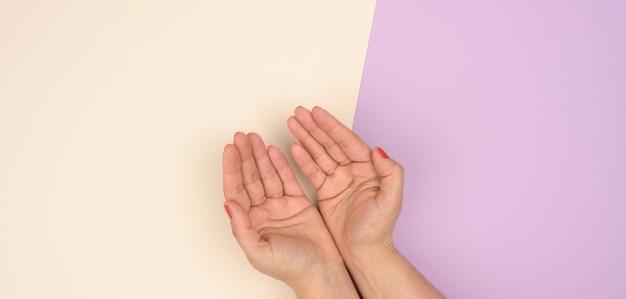 Deux mains féminines pliées paume contre paume sur une surface violette beige, vue de dessus