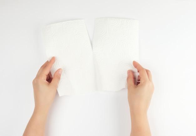 Deux mains féminines tenant une serviette en papier blanc propre pour le visage et le corps