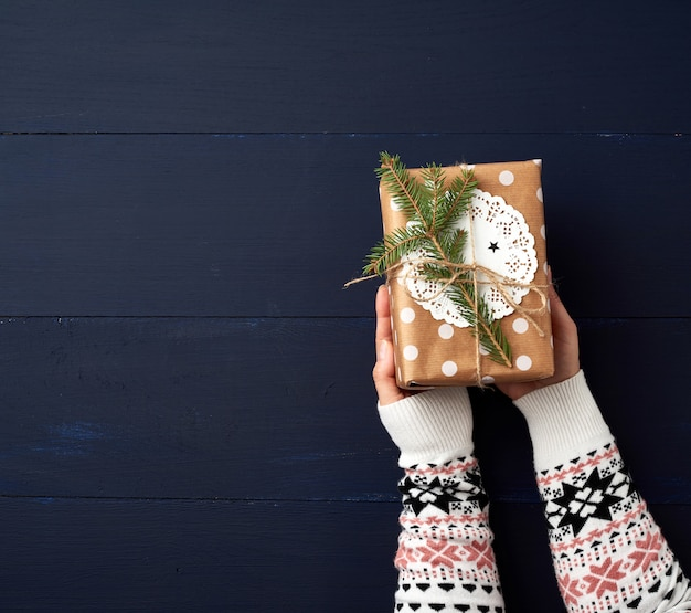 Deux mains féminines tiennent une boîte fermée en papier sur un bois bleu. concept festif
