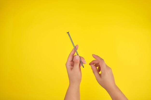 Deux mains féminines tiennent un grand clou de fer, fond jaune,