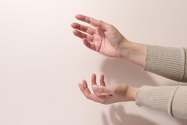 Deux mains féminines tiennent n'importe quel objet sur un fond beige. présentation des produits, cosmétiques