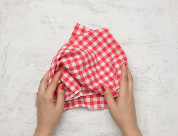 Deux mains féminines tiennent une serviette de cuisine en textile à carreaux blancs-rouges froissés sur une table blanche, vue de dessus