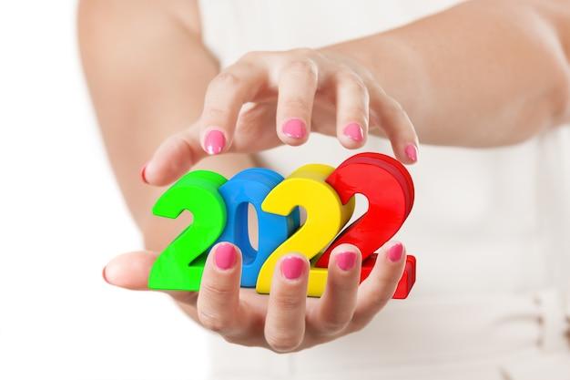 Deux mains de femme protégeant le signe du nouvel an 2022 sur fond blanc.
