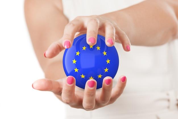 Deux mains de femme protégeant la sphère du globe terrestre du drapeau de l'union européenne sur un fond blanc.