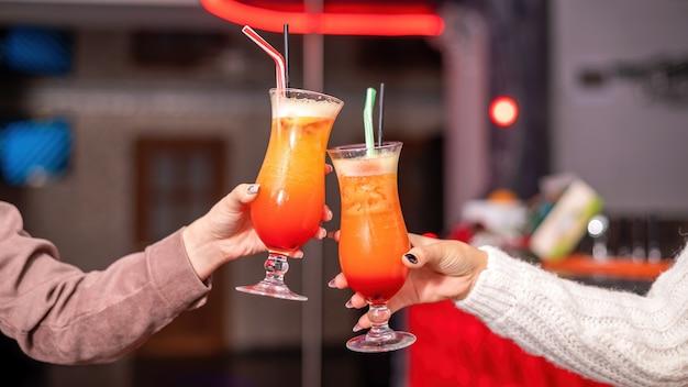 Deux mains de femmes tinter les verres avec des cocktails dans un restaurant