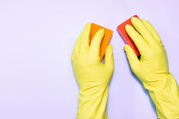 Deux mains d'homme dans des gants en caoutchouc avec une éponge sur fond violet.