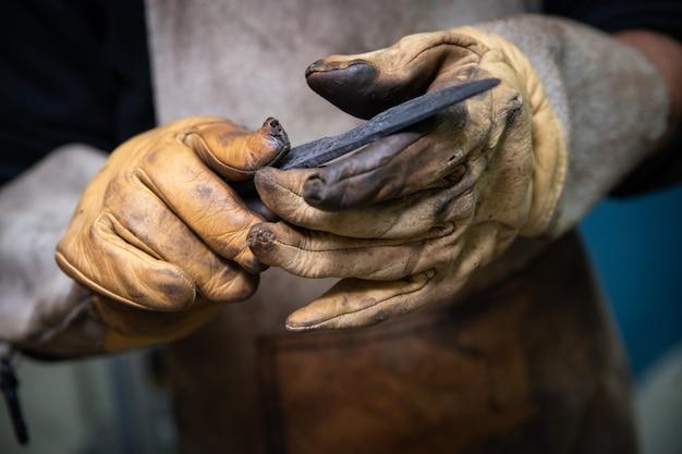 Deux mains d'homme fabriquent un couteau en acier