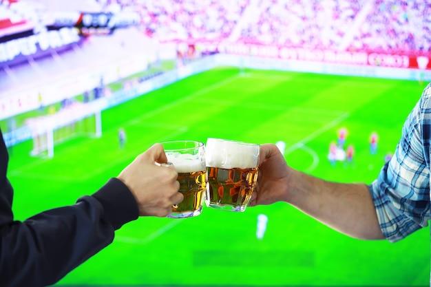 Deux mains horizontales tenant un verre de bière blonde et tintement sur fond de match de football. les amateurs de sport se réjouissent. concept de mode de vie de loisirs d'amis.