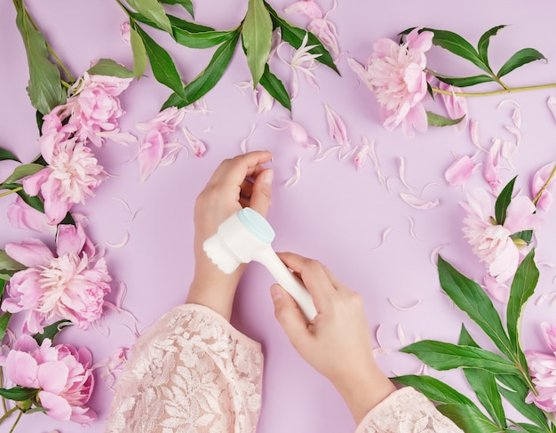 Deux mains d'une jeune fille à la peau lisse et un bouquet de pivoines roses