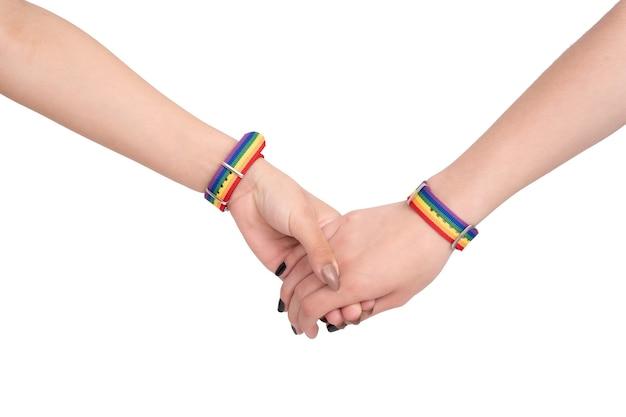 Deux mains jointes avec des bracelets lgbt de couleur arc-en-ciel sur blanc