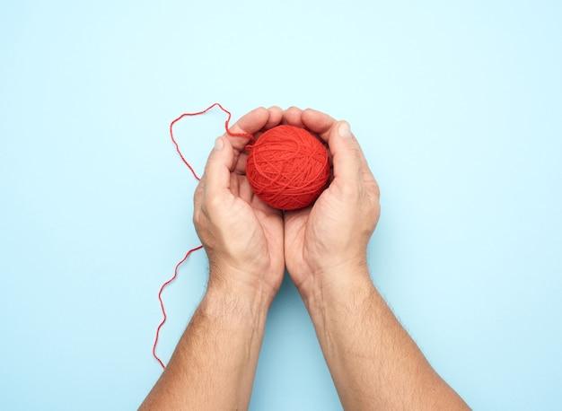 Deux mains mâles tiennent une boule de fils de laine rouge vue de dessus