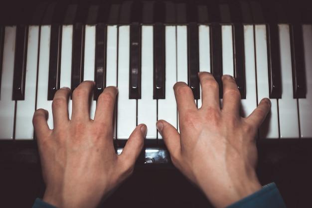 Deux mains masculines sur le piano.