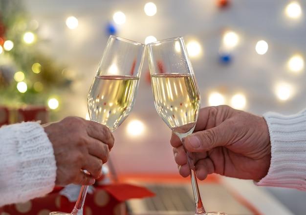 Deux mains de peuples grillant avec un verre de vin scintillant célébrant les vacances de noël