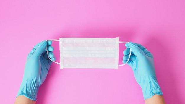 Deux mains portent des gants bleus et tiennent un masque facial pour se protéger des infections virales. mettez sur fond rose.