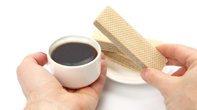 Deux mains avec une tasse de café noir et une gaufre. desserts