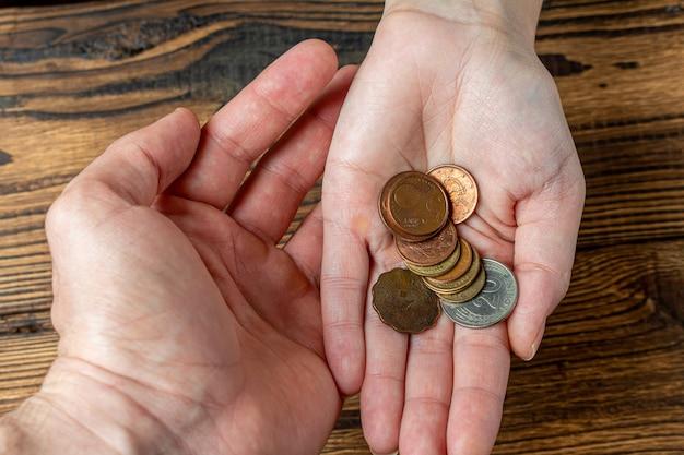 Deux mains tenant des pièces dans les paumes. partage, charité, concept de famille.