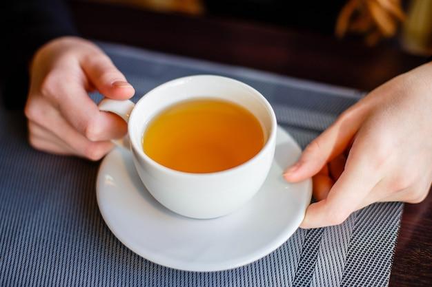 Deux mains tenant une tasse en porcelaine à l'heure du thé au café