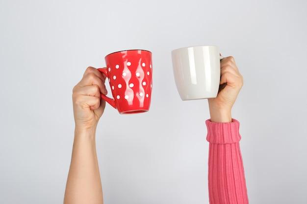 Deux mains tenant des tasses en céramique sur blanc