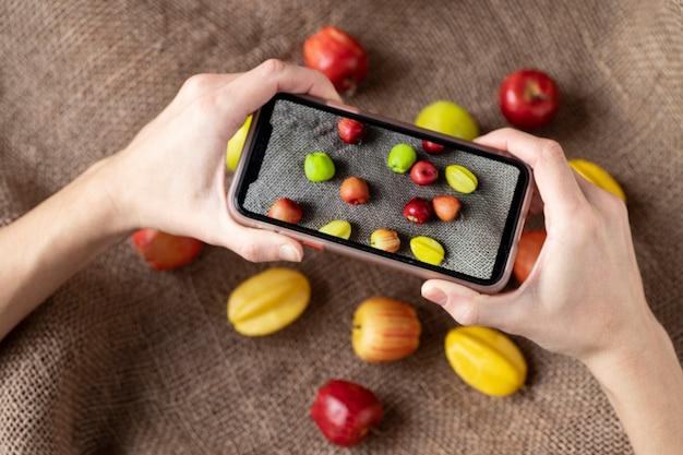 Deux mains tiennent un téléphone avec une photo et des pommes caramboles allongées sur un sac.