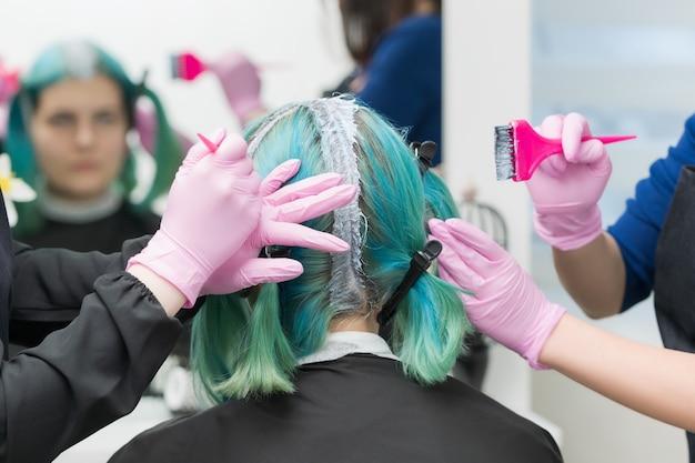Deux maîtres coiffeurs professionnels appliquent de la peinture sur les cheveux des femmes pendant le processus de décoloration des racines des cheveux