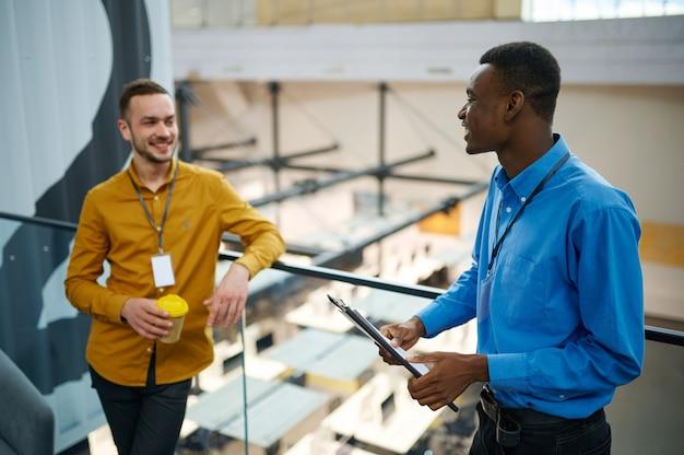 Deux managers discutant sur le balcon du bureau informatique