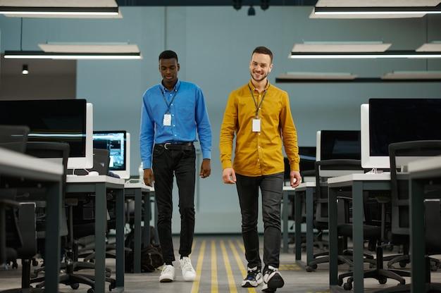 Deux managers masculins souriants au bureau informatique. travail d'équipe et planification professionnels, remue-méninges de groupe, intérieur d'entreprise moderne en arrière-plan, employés qui réussissent