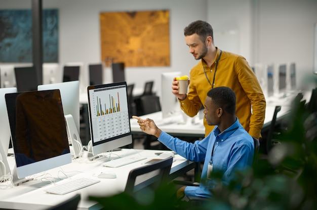 Deux managers masculins travaillent sur ordinateur dans un bureau informatique. travail d'équipe et planification professionnels, remue-méninges de groupe, intérieur d'entreprise moderne en arrière-plan