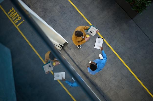Deux managers parlent au bureau informatique, vue de dessus