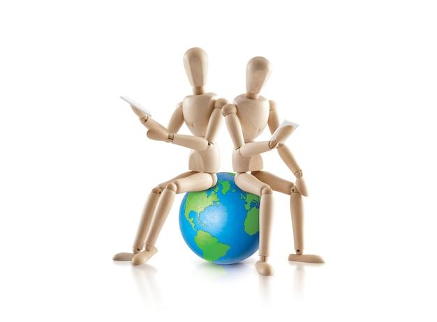 Deux mannequins en bois assis sur le monde