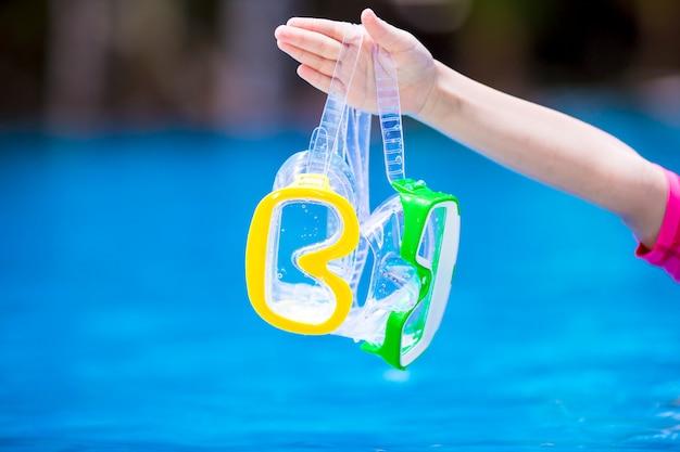 Deux masques de plongée humides dans la main de l'enfant près de la piscine