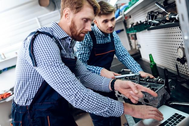 Deux mécaniciens automobiles travaillent ensemble dans un garage.